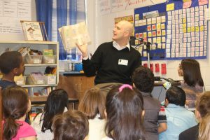 Guest reader reading to children in classroom