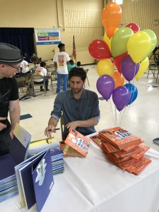 Author signing Books at Storybus Event